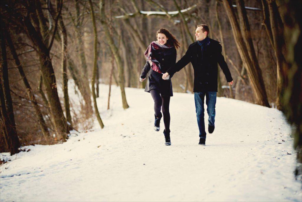 Liebesgeschichte Paar läuft die Kamera entgegen in Wintergewand